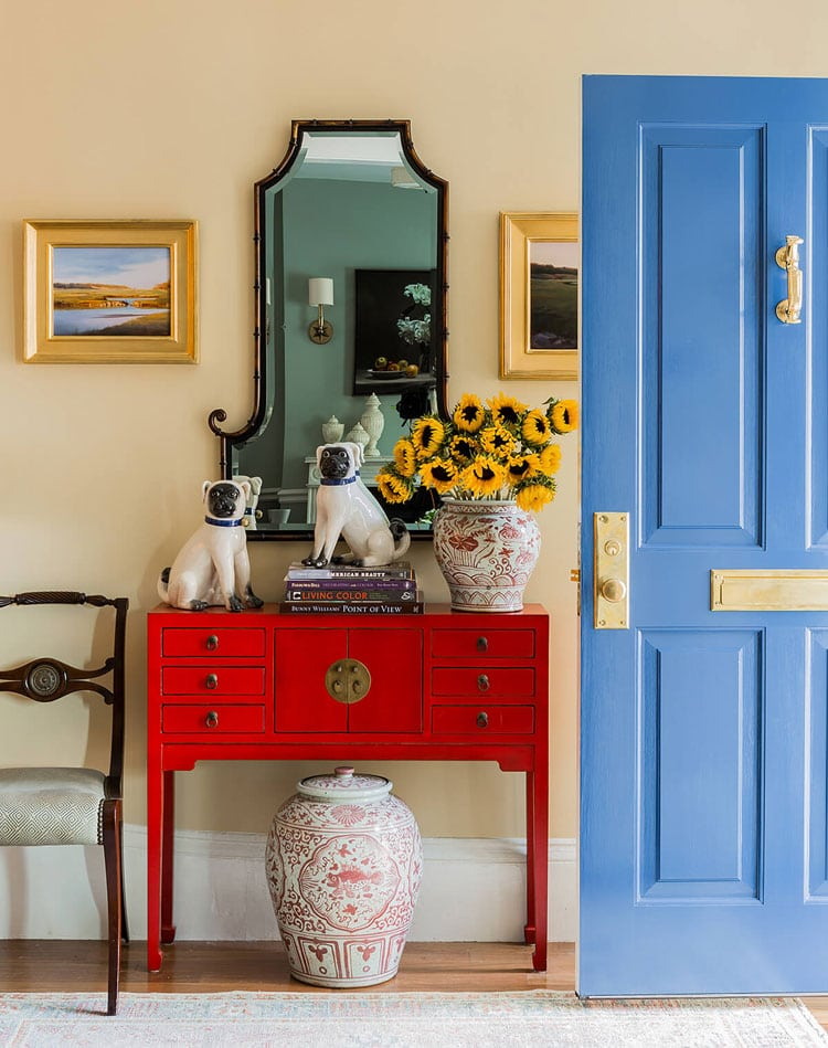 Colorful Foyer Decor with Red Table, Blue Door, Yellow Frames, and Mirror