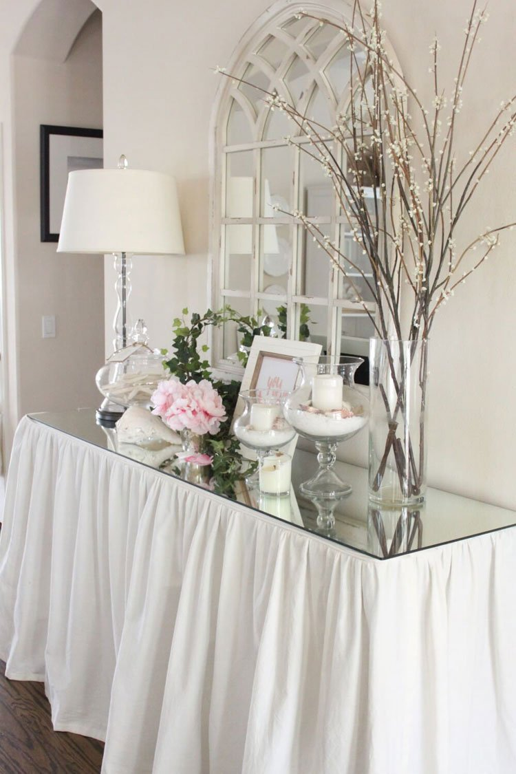 Glass Foyer Table with a Unique Wall Mirror, White Linen Cloth, and Several Chic Decorating Ideas